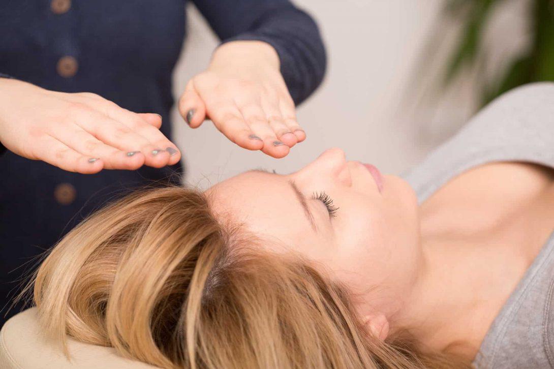 Foto van vrouw die ligt op een massage tafel terwijl ze healing ontvangt van 2 handen die je in de foto ziet. Reconnective healing helpt je weer in balans te komen en terug op je levenspad zodat je het leven gaat leven waarvoor je hier op aarde bent gekomen.