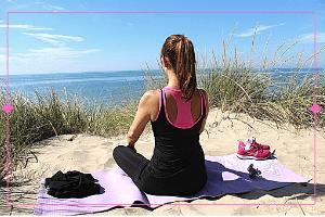 Foto van mediterende vrouw die in rust na afloop van haar yoga sessie in de duinen mediteert met uitzicht op de zee