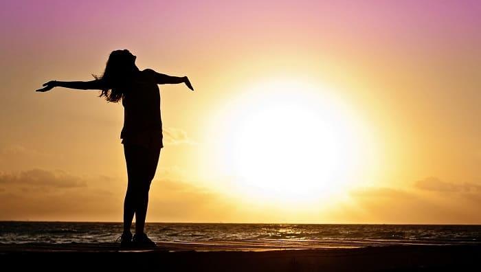 Foto van vrouwelijk silhouet voor een ondergaande zon aan het strand. Ze drukt een gevoel van vrijheid en innerlijke rust uit
