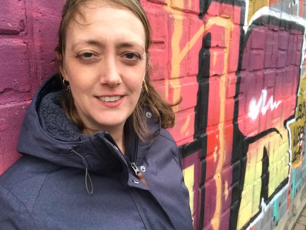 Foto van Suzanne Lommers, die je uitnodigt haar te volgen via Facebook, LinkedIn en Instagram. Toffe graffiti muur op de achtergrond