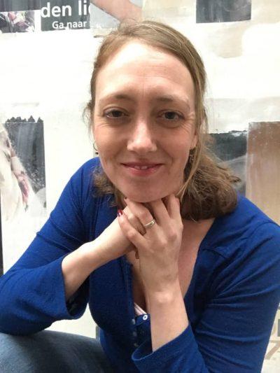 Foto van Suzanne Lommers die je recht aan kijkt. Stress less en live purely is mijn uitnodiging aan jou