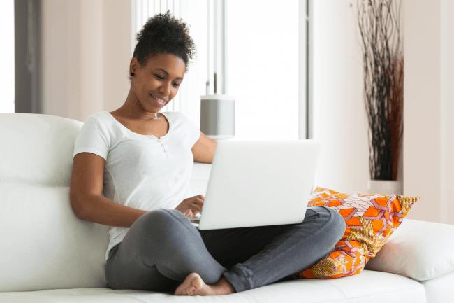 Prachtige donkere vrouw die met laptop op de bank zit. Ze glimlacht en denkt ja ik meld me aan voor de gratis reconnection cursus