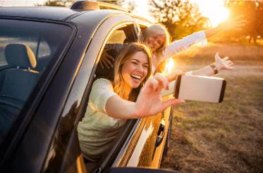 Sommige moeders bouwen geen ruimte in om je te vervelen. Twee vrouwen die uit een auto leunen en uitgelaten foto's maken van henzelf met de zonsondergang.