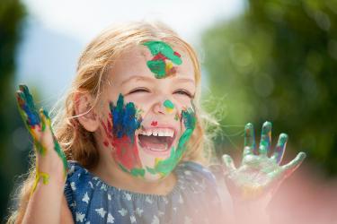 Je vervelen maakt moeders en kinderen creatief. Meisje die met haar gezicht en handen onder de verf zit. Ze lacht breed en is helemaal blij en uitgelaten