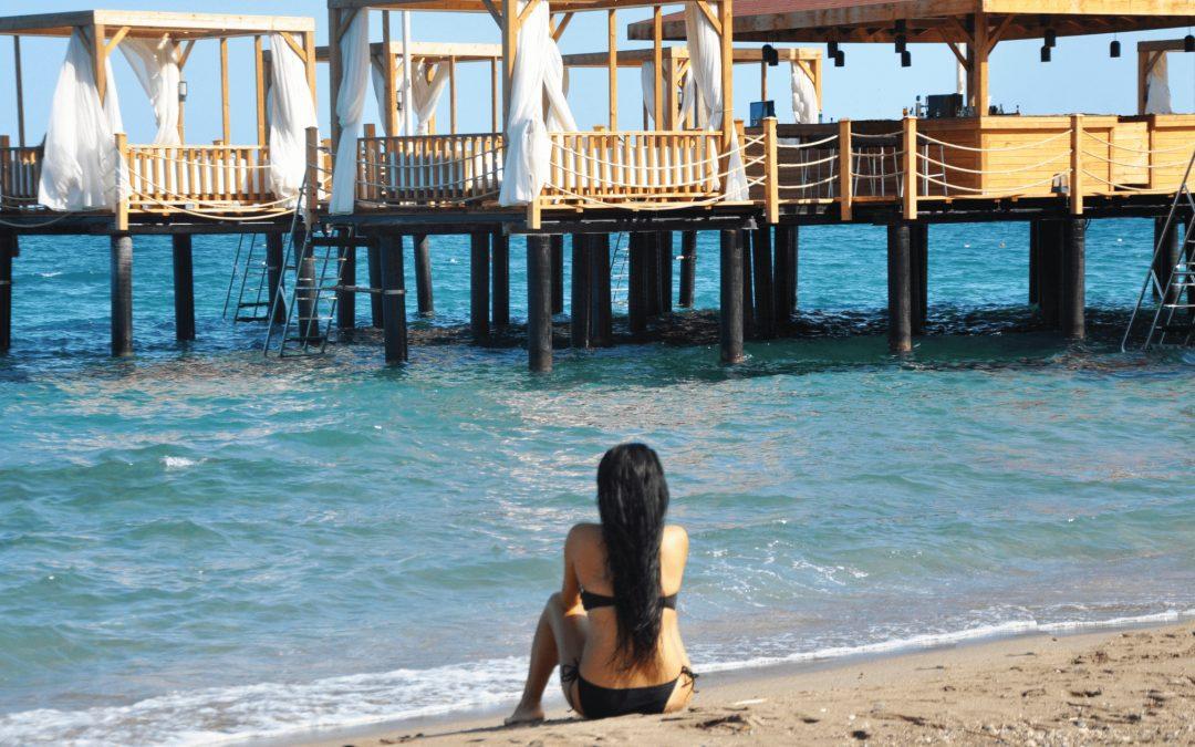 Waar je ook bent, je vervelen is een mooi cadeau wat je jezelf kan geven. Deze vrouw zit in bikini op het strand aan de rand van het water en staart in de verte naar een rijtje hutten op palen in het water. Ze doet niets.