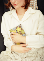 Vrouw die in stoel zit, zich te vervelen met een dagboek in haar handen. Ze geeft ruimte aan verveling om zichzelf te voelen